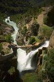 Brug over een waterval onder groene heuvels stock afbeelding