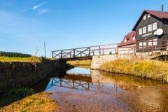 Brug over Jizerka-kreek bij oude houten hut - Oude Zaagmolen, Tsjech: Starapila, op zonnige de zomerdag Jizerkadorp stock foto