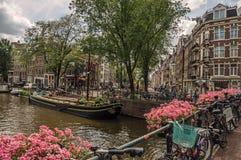 Brug over kanaal met bloemen, fietsen, oude gebouwen en boten in Amsterdam Royalty-vrije Stock Afbeeldingen