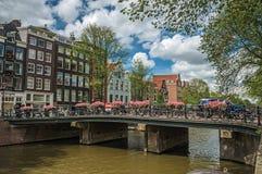 Brug over kanaal met oude gebouwen, mensen en fietsers die door in Amsterdam overgaan Royalty-vrije Stock Foto's