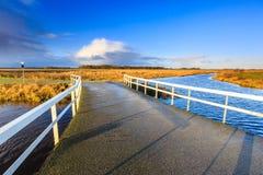 Brug over rivier in een landelijk landschap dat door ochtendzon wordt aangestoken Stock Foto
