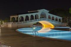 Brug over zwembad in hotel met nachtverlichting stock foto's