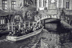BRUGES, BÉLGICA - 17 DE JANEIRO DE 2016: Transporte o barco com turistas que olham na construção antiga da cidade medieval Fotografia de Stock