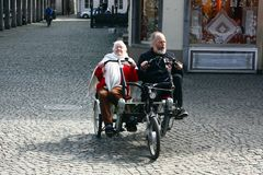 BRUGES BELGIEN 03 26 2018 äldre parturister rider en sida - vid - den tandema cykeln för sidan arkivfoton