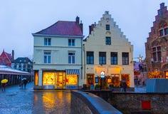 Bruges Belgien - December 13, 2017: Folket som går nära historiska medeltida byggnader längs en kanal i Bruges Arkivfoton
