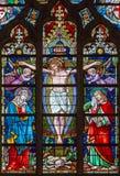 BRUGES BELGIEN - JUNI 12, 2014: Korsfästelsen på fönsterrutan i domkyrka för St Salvators Royaltyfri Fotografi