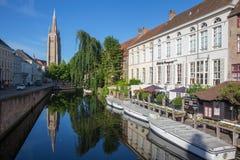 BRUGES BELGIEN - JUNI 12, 2014: Se till kanalen från den Sint Jan Nepomucenus bron med tornet av vår damkyrka i morgon Arkivbild