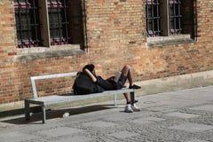 BRUGES BELGIEN -03 27 2017 läser en ung man en bok på en bänk med hans skor som tas av arkivbild