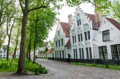 Bruges Belgien - Maj 11, 2015: Hus för folkbesökvit i Beguinagen (Begijnhof) i Bruges Royaltyfri Fotografi