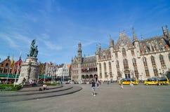 Bruges Belgien - Maj 11, 2015: Turist på den Grote Markt fyrkanten i Bruges, Belgien Royaltyfri Foto
