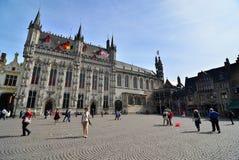 Bruges Belgien - Maj 11, 2015: Turist på småstadfyrkant med stadshuset i Bruges Arkivbilder