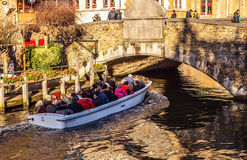 BRUGES, BELGIO - 17 GENNAIO 2016: Trasporti la barca con i turisti che considerano la costruzione antica della città medievale Immagine Stock Libera da Diritti