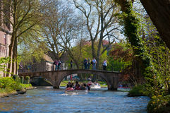 Bruges, Belgium - April 10 : Unidentified tourists visit the medieval city of brugge using the typical boats over canals in Bruges Stock Photos