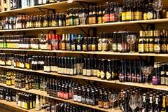 BRUGES/BELGIUM - 14 aprile 2014: Le bottiglie di birra da vendere sopra spostano Immagine Stock