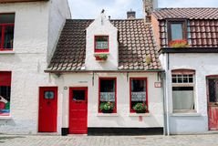 Bruges, Belgium - August 2010: Small picturesque white houses with red doors, red window frames, red flowers and red roof tiles stock images