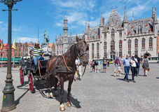 BRUGES, BELGIUM - JUNE 13, 2014: The Carriage on the Grote Markt and the Provinciaal Hof building Royalty Free Stock Images