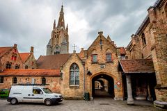 BRUGES, BELGIUM - JUNE 10, 2014: View of Church of Our Lady in Bruges. BRUGES, BELGIUM - JUNE 10, 2014: Outside view of Church of Our Lady in Bruges. Its tower Stock Photo