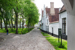 Bruges, Belgium - May 11, 2015: People visit White houses in the Beguinage in Bruges, Belgium. Bruges, Belgium - May 11, 2015: People visit White houses in the royalty free stock photo