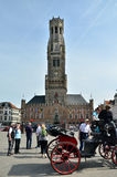 Bruges, Belgium - May 11, 2015: Tourist visit Belfry of Bruges on Grote Markt square Stock Image