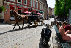Bruges, Belgium - May 11, 2015: Tourists visit Bruges in traditional horse carriage around the city Stock Images