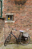 Bruges. BELGIUM - OCTOBER, 25: Bike next to a brick wall in which there is a window with an artificial flower, on October25, 2013, in , Belgium Stock Photo