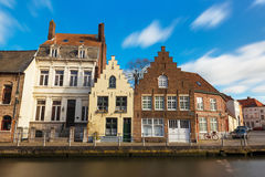 Bruges (Brugge), Belgium, February 2016: Old  belgian street with traditional varicolored  houses and water canal Stock Photos