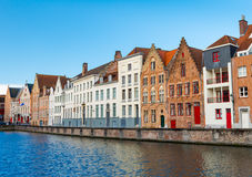 Bruges (Brugge), Belgium - February 2016: Typical belgian street with traditional medieval brick houses and water canal Royalty Free Stock Photography