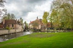 Bruges (Brugge) kanal med svanen på bron och porten till Beguinage Fotografering för Bildbyråer