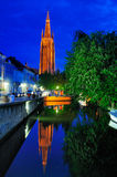 Church of Our Lady by Night - Bruges. Bruges (Brugge) by night. This picture show the Onze-Lieve-Vrouwekerk (Church of Our Lady) with one of the canals in the Royalty Free Stock Photography