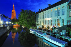 Church of Our Lady by Night - Bruges. Bruges (Brugge) by night. This picture show the Onze-Lieve-Vrouwekerk (Church of Our Lady) with one of the canals in the Stock Image