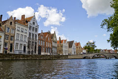 Bruges Canal And Clouds. Bruges Canal with homes. All faces are unrecognizable and blurred in the distance Royalty Free Stock Image