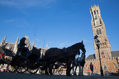 Bruges - The Carriage on the Grote Markt and Belfort van Brugge in background. Royalty Free Stock Image