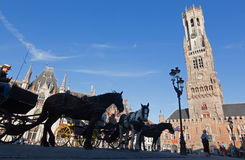 Bruges - The Carriage on the Grote Markt and Belfort van Brugge Stock Image