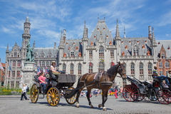 Bruges - The Carriage on the Grote Markt and the Provinciaal Hof building in background. Stock Image