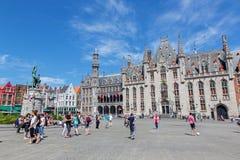 Bruges - Groten Markt, Provinciaal Hof den gotiska byggnaden och Historium byggnad Royaltyfria Foton