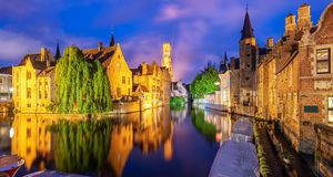 The Bruges historical Old Town, Belgium, an UNESCO World Culture Heritage site. Panoramic view of the Rozenhoedkaai canal, historical brick houses and the Belfry royalty free stock image