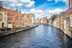 Bruges kanal, byggnader, kyrka och en installation för metalltråd på royaltyfri bild