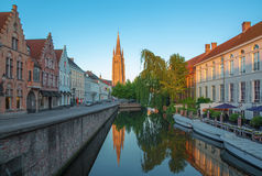 Bruges - Look to canal from Sint Jan Nepomucenus bridge with the tower of Our Lady church in morning Stock Photography