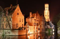 Bruges by night. (Belgium). Old houses near the waterfront with belfry tower at the background Stock Photos