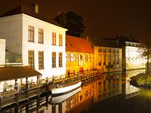Bruges by night. Calm Dijver canal with boat in the dock. Belgium Royalty Free Stock Photo