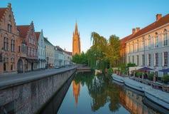 Bruges - olhe ao canal da ponte de Sint Jan Nepomucenus com a torre de nossa igreja da senhora na manhã Fotografia de Stock