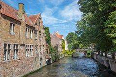 Bruges - olhe da rua de Steenhouwersdijk às casas do canal tipicamente Fotografia de Stock Royalty Free