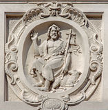 Bruges - relief of st. John the Baptist on he facade of baroque Carmelites church. Stock Photos