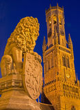 Bruges - Statue of lion before of the Provincial hof building and Belfort van Brugge. Royalty Free Stock Photography