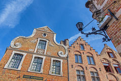 Bruges - Typically brick house and Madonna statue on the edge of street. Stock Image