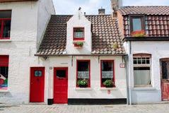 Brugge, België - Augustus 2010: Kleine schilderachtige witte huizen met rode deuren, rode raamkozijnen, rode bloemen en rode dakt stock afbeeldingen