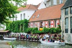 Brugge, België - Augustus 2010: Toeristen die zich in een rij op de pijler voor hun rondvaart langs de kanalen van de stad bevin stock fotografie