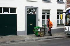 BRUGGE, BELGIË 03 26 2018 duwt een hygiënearbeider gekleed in specifiek materiaal een karretje met dumpster cansg stock afbeeldingen