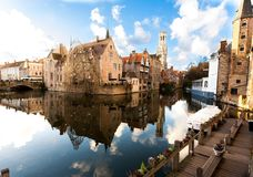 Brugge Belgien: Medeltida hus och gotiskt klockatorn som reflekterar på vatten, under en solig vinterdag royaltyfria foton