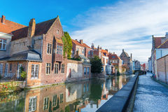 Brugge, Belgium: View of typical street of medieval city of Bruges with traditional architecture, canal and walking people Stock Photo